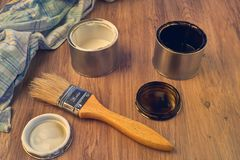 Paint cans, brush and rag, tools for painting. Black and white paint bucket with brush and dirty rag on wooden background royalty free stock images