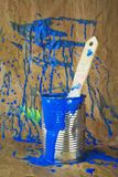 Paint can with brush and blue paint splatters Stock Photography