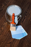 Paint can and brush with samples. A paint can and paint brush with blue paint chip samples on a hardwood floor Royalty Free Stock Images