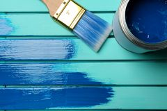 Paint can, brush and stroke on blue wooden background. Top view. Space for text royalty free stock photos