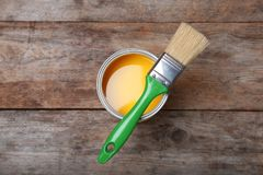 Paint can and brush on wooden background. Top view royalty free stock photo