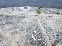 Paint can lid and white paint spilled on cement sidewalk and asphalt road. Paint can lid and white paint spilled on cement sidewalk or pavement and asphalt road stock image