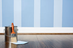 Paint can and painted wall. A paint can with paint brush and paint chips on hardwood floor against a blue striped tone on tone painted wall Stock Photo