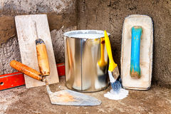 Paint can and tools on a concrete wall. Paint can, trowels and spirit level above a rough unfinished concrete surface royalty free stock images