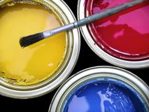 Paint Cans. Three paint cans with one brush on top Royalty Free Stock Image