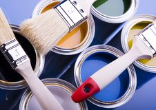Paint and cans. Cans with paint and brushes on the blue background royalty free stock photography
