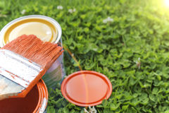 Paint cans, brushes, bright orange color. All on a background of green grass stock photos
