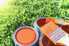 Paint cans, brushes, bright orange color. All on a background of green grass royalty free stock photos