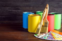 Paint cans, brushes and color palette sample on table. Against wooden background. Space for text stock photos