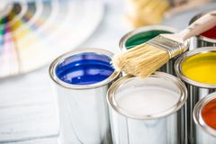 Paint cans brushes and color palette on table.  royalty free stock image