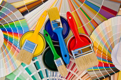Paint cans and brushes on color stripes of sample. Stock Photo