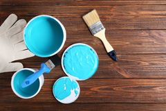 Paint cans, brushes and gloves on wooden table royalty free stock photos