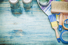 Paint cans brushes pantone fan adhesive tape on wooden board Stock Photos