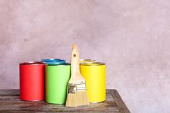 Paint cans and brushes on table. Against color background. Space for text royalty free stock images