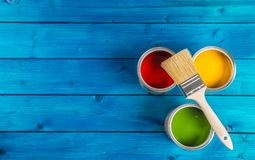 Paint cans color palette, cans opened with brushes on blue table.  royalty free stock images