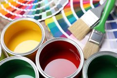 Paint cans, color palette samples and brushes on table. Closeup view stock photo
