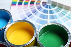 Paint cans and color palette samples on table. Closeup stock photography