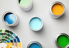 Paint cans and color palette on white background. Top view stock image
