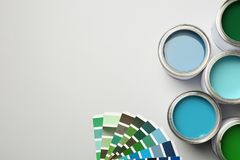 Paint cans and color palette on white background, top view. Space for text royalty free stock photo