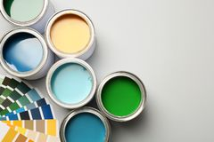Paint cans and color palette on white background, top view. Space for text royalty free stock photos