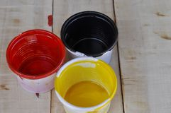 Paint cans color palette on wooden table, Red, yellow and black color on wooden table. Art blue artist background colorful house container decoration metal stock images