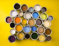 Paint cans color palette, yellow background. Full Buckets of rainbow colored oil paint on red background royalty free stock images