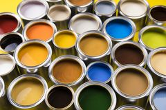 Paint cans color palette, yellow background. Full Buckets of rainbow colored oil paint on red background royalty free stock photography