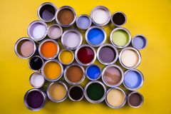 Paint cans color palette, yellow background. Full Buckets of rainbow colored oil paint on red background royalty free stock image