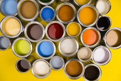 Paint cans color palette, yellow background. Full Buckets of rainbow colored oil paint on red background stock photos