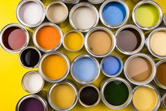 Paint cans color palette, yellow background. Full Buckets of rainbow colored oil paint on red background royalty free stock photo
