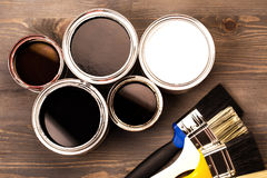 Paint cans and colored brushes. House renovation, paint cans and colored brushes on the wooden grey background Stock Image