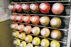 Paint cans are sold in the store. Showcase with metal cans of different colors with paint for drawing. The concept of graffiti and. Paint cans are sold in the stock photo