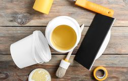 Paint cans and tools on wooden table royalty free stock images