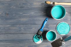 Paint cans and tools on wooden table royalty free stock image