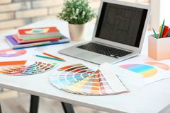 Paint color palette samples and laptop. On table indoors stock image