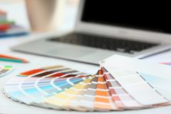 Paint color palette samples and laptop on table Stock Photography