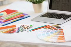 Paint color palette samples and laptop on table Stock Photos
