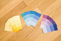 Paint color swatches. Paint color swatches grouped together by color on wood floor Stock Photos