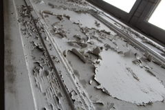 Paint coming off the wall cracked paint white wood. White paint coming off the wall cracked paint wood next to a window frame royalty free stock photo