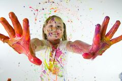 Paint covered hands. A child covered in colorful paint showing her hands Stock Photos