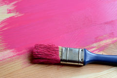Paint-covered paintbrush on painted wood Stock Photos