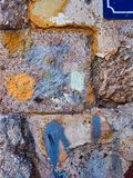 Paint Daubs on Rough Stone Blocks in Old House Wall. Detail of roughly hewn stone blocks in a traditional, old and original Greek house, with colourful graffiti stock image
