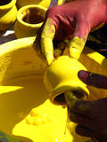 Paint Dip. A potter clearing the extra paint on a pot after dipping it in a vessel containing yellow paint Stock Photos