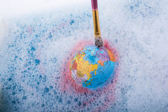 Paint dissolving on the top of globe Stock Photography