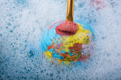 Paint dissolving on the top of globe Royalty Free Stock Photography