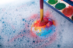 Paint dissolving on the top of globe Stock Photos
