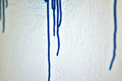 Paint drip. White wall with blue dripping paint. Selective focus Royalty Free Stock Image