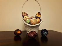Easter egg basket, ilustration, backgrounds. Paint eggs in vibrant colors: yellow, gold, copper, red, green, silver. Eggs have different patterns lance, pansies Stock Photos