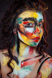 Paint on the face of a young girl. On a black background Royalty Free Stock Photos