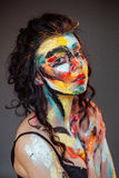 Paint on the face of a young girl. On a black background Royalty Free Stock Photography